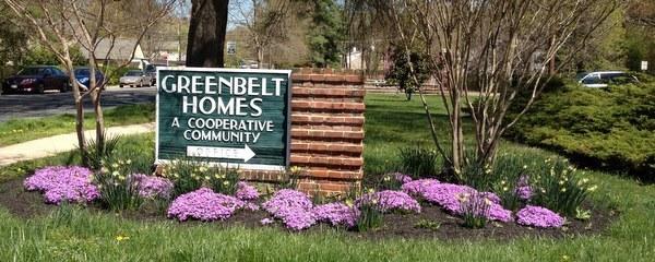 Entrance sign for Greenbelt Homes in spring